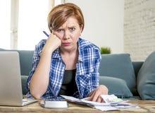年轻红色头发白种人妇女大约运作文书工作国内财务会计和银行业务的30岁看起来压下 免版税库存照片
