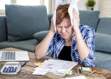 年轻红色头发白种人妇女大约运作文书工作国内财务会计和银行业务的30岁看起来压下 免版税图库摄影