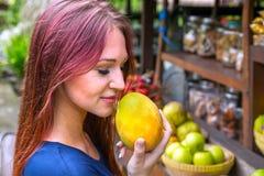 年轻红色顶头妇女嗅到成熟黄色芒果 免版税图库摄影