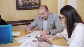 年轻经理和院长企业配合在严肃和活跃混乱会议期间,与纸和报告一起使用 股票录像