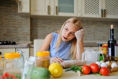 年轻绝望主妇在她的厨房里 免版税库存照片