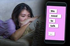 年轻绝望和哀伤的亚洲韩国女人感觉在网上压下了与手机的遭受的痛苦和伤心综合 库存图片