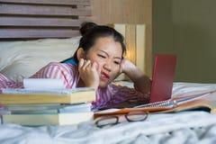 年轻绝望和疲乏的亚洲中国大学生女孩感觉淹没了并且强调了准备学习与的检查 库存图片