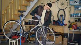 年轻维修员装配安置stearing的轮子和修理它的自行车,当听到与耳机时的音乐 股票录像