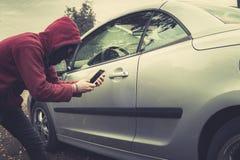 年轻罪犯侧视图黑巴拉克拉法帽和有冠乌鸦藏品智能手机和设法的与汽车互动由机动性 免版税库存图片