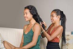 年轻美丽和愉快的亚裔女朋友在家横卧与掠过另一妇女帮助的头发的一个女孩为做准备 免版税库存图片