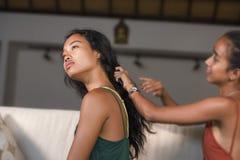 年轻美丽和愉快的亚裔女朋友在家横卧与掠过另一妇女帮助的头发的一个女孩为做准备 库存图片
