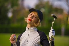 年轻美丽和愉快的妇女户外生活方式画象打的举行球和轻击棒俱乐部微笑的高尔夫球快乐在st 免版税图库摄影