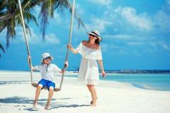 年轻美丽的一个热带海滩的妇女摇摆的儿子,酸值Phangan海岛 泰国 免版税库存图片
