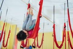 年轻美丽的与一个吊床的女子实践的瑜伽飞行在明亮的演播室 飞行,健身,舒展,平衡 免版税库存照片
