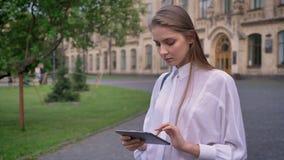 年轻美丽的严肃的女孩在她的片剂工作在夏天,通信概念 股票视频