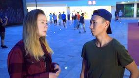 年轻美丽的亚裔夫妇、人和女孩互相谈话,站立在城市的街道上 股票录像