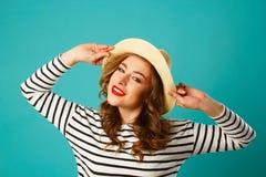 年轻美丽的兴高采烈的白肤金发的妇女画象帽子的在蓝色 库存图片