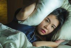 年轻美丽的哀伤和沮丧的亚裔中国妇女家庭生活方式画象醒在床夜间遭受的忧虑危机 免版税库存图片