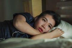 年轻美丽的哀伤和沮丧的亚裔中国妇女家庭生活方式画象醒在床夜间遭受的忧虑危机 免版税库存照片