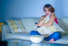 年轻美丽的哀伤的拉丁吃玉米花的妇女观看的戏曲浪漫电影在家坐沙发长沙发夜间在悲伤面孔 库存照片