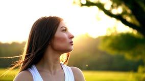 年轻美丽的在公园的妇女听的音乐,当跑时 微笑的运动的女孩画象有看的耳机的 影视素材