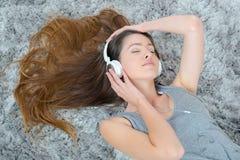 年轻美丽的在地板上的妇女耳机听的音乐 免版税库存照片