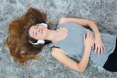 年轻美丽的在地板上的妇女耳机听的音乐 库存照片