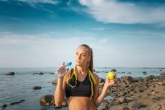 年轻美丽的在海滩的女运动员饮用水与测量的磁带 库存照片