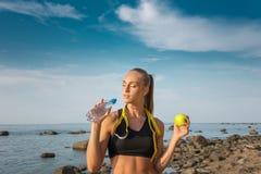 年轻美丽的在海滩的女运动员饮用水与测量的磁带 免版税库存图片