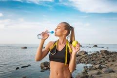年轻美丽的在海滩的女运动员饮用水与测量的磁带 免版税图库摄影