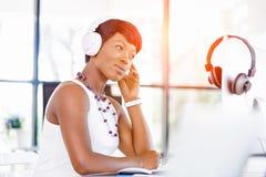 年轻美丽的在耳机的女实业家听的音乐 免版税库存照片