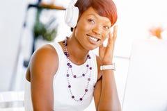 年轻美丽的在耳机的女实业家听的音乐 图库摄影