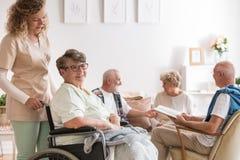 年轻美丽的坐在轮椅的照料者和正面资深妇女在老人的老人院 免版税库存照片