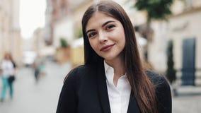 年轻美丽的女商人或学生画象衣服的 她微笑,愉快,身分在市中心 概念:新 股票录像