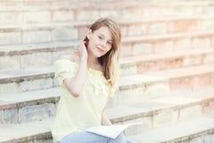 年轻美丽的女学生在台阶读 免版税图库摄影