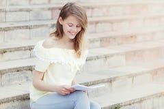 年轻美丽的女学生在台阶读 图库摄影