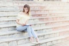 年轻美丽的女学生在台阶读 免版税库存图片