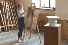 年轻美丽的女学生画与一支铅笔的多立克体资本在一个木画架作为她的大学任务 免版税库存照片