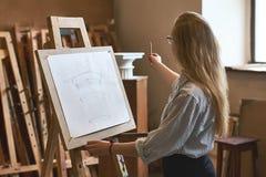 年轻美丽的女学生画与一支铅笔的多立克体资本在一个木画架作为她的大学任务 图库摄影