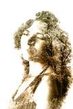 年轻美丽的女孩两次曝光在叶子和树中的 库存照片