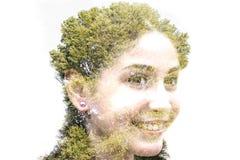 年轻美丽的女孩两次曝光在叶子和tre中的 免版税库存图片