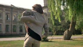 年轻美丽的女孩在公园跳舞自白天,在夏天,运动概念,修造在背景, blured 股票录像