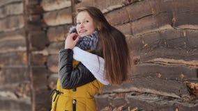 年轻美丽的女孩在冬天给正面摆在穿衣在一个木房子的背景的照相机在 股票录像