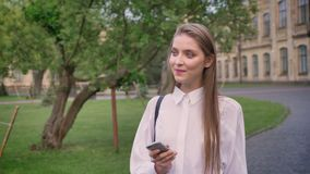年轻美丽的女孩在夏天,想法的过程,通信概念键入在她的智能手机的消息 股票录像