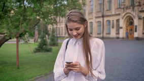 年轻美丽的女孩在夏天,调情的人构想,通信概念键入在她的智能手机的消息 股票视频