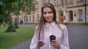 年轻美丽的女孩在夏天,通信概念键入在她的智能手机的消息用咖啡 股票视频
