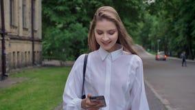年轻美丽的女孩在她的智能手机观看,进来在公园在夏天,通信概念 股票录像