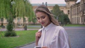 年轻美丽的女孩在她的智能手机读消息在夏天,通信概念 股票录像
