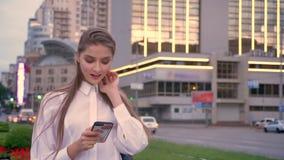 年轻美丽的女孩在市中心键入在她的智能手机的消息在日落在夏天,通信概念 影视素材