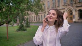 年轻美丽的女孩在电话谈话在公园在夏天,听,通信概念 股票录像