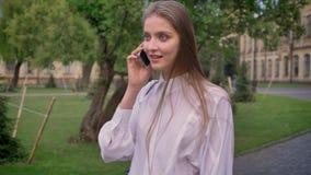 年轻美丽的女孩在电话谈话在公园在夏天,通信概念 股票录像