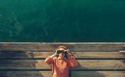 年轻美丽的女孩在码头说谎在海附近并且通过在天空的双筒望远镜看 旅行查寻旅途概念 图库摄影