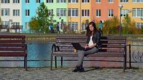 年轻美丽的女孩坐一条长凳在公园 在膝上型计算机的工作 股票视频