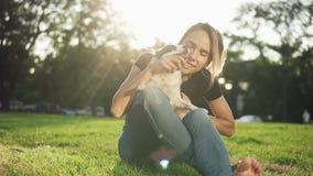年轻美丽的女孩坐与她的狗的草 逗人喜爱女性使用与宠物室外在自然 3d明亮的重点拥抱亲吻红色翻译 股票视频